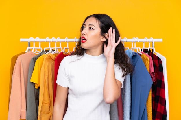 Race mélangée, femme, dans, a, magasin vêtements, écoute, quelque chose