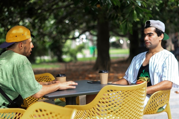 Une race mixte d'amis mangeant ensemble de la nourriture de rue assis à table