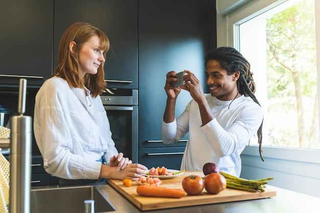Race mixte couple coupant des légumes ensemble dans la cuisine.