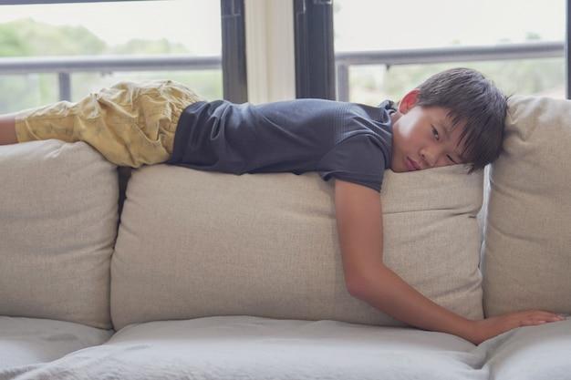 Race mixte garçon asiatique préadolescent se sentir ennuyé allongé sur le canapé à la maison, distanciation sociale, quarantaine, concept d'isolement, sensibilisation à l'autisme, santé mentale