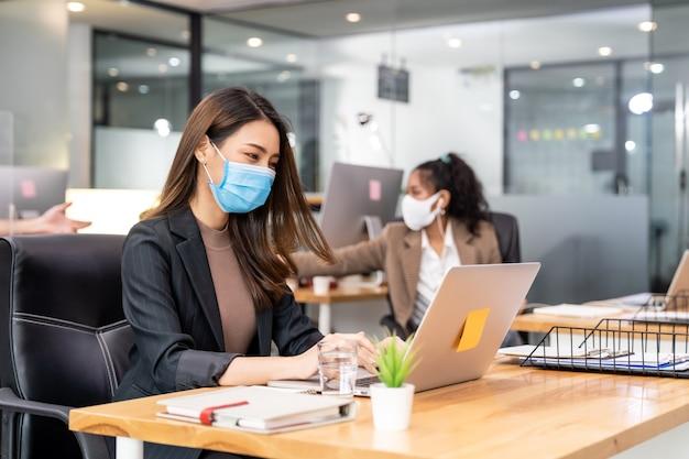 Race mixte de gens d'affaires africains et asiatiques portant des masques au bureau