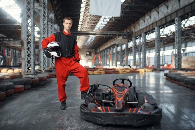 Racer avec casque pose près de go kart car, karting auto sport indoor. course de vitesse sur piste de karting étroite avec barrière de pneu. compétition de véhicules rapides, loisirs à haute adrénaline