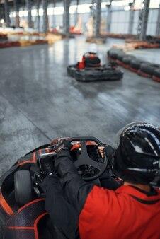 Racer in casque conduisant une voiture de karting, vue arrière, karting auto sport indoor. course de vitesse sur piste de karting étroite avec barrière de pneu. compétition de véhicules rapides, passe-temps à haute adrénaline