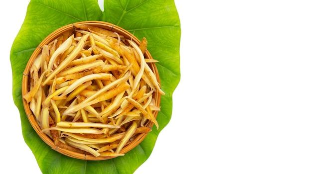 Racine de doigt coupée en tranches dans le panier en bambou sur la feuille verte