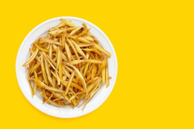 Racine de doigt en tranches en plaque blanche sur fond jaune.