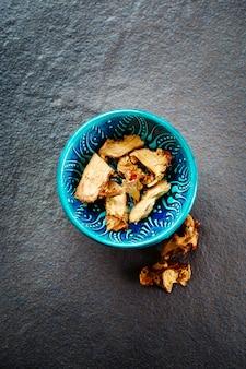 Racine de galanga séchée dans un bol oriental authentique
