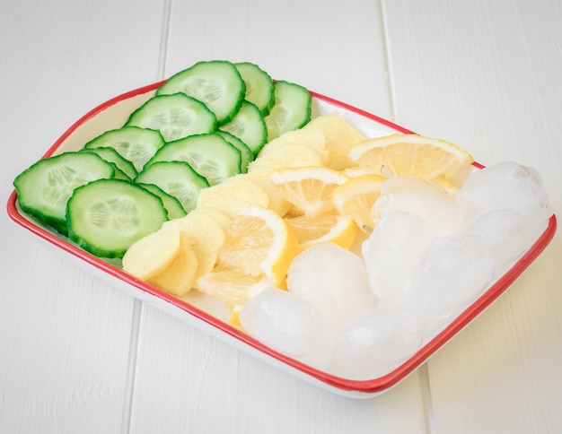 Racine de gingembre, citron, concombre, glace sur une table en bois blanche.