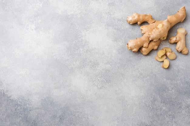 Racine de gingembre frais sur une surface grise. .