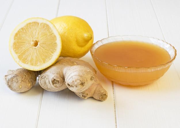 La racine de gingembre et de miel sur une table en bois blanche.