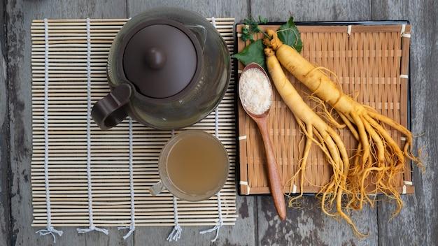 Racine de ginseng frais avec une tasse de thé chaud, le concept de boisson saine