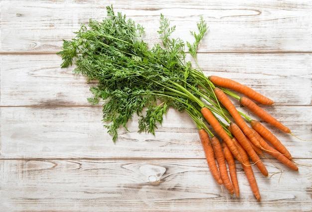 Racines de carottes fraîches avec des feuilles vertes sur fond de bois. concept d'aliments biologiques