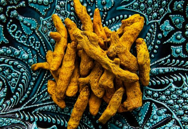 Racines de curcuma sèches entières sur une assiette décorative