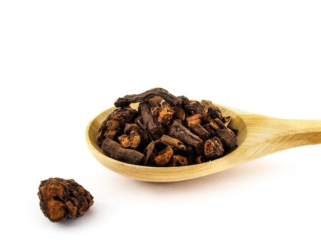 Les racines de rubia ou marena se trouvent dans une cuillère en bois sur fond blanc