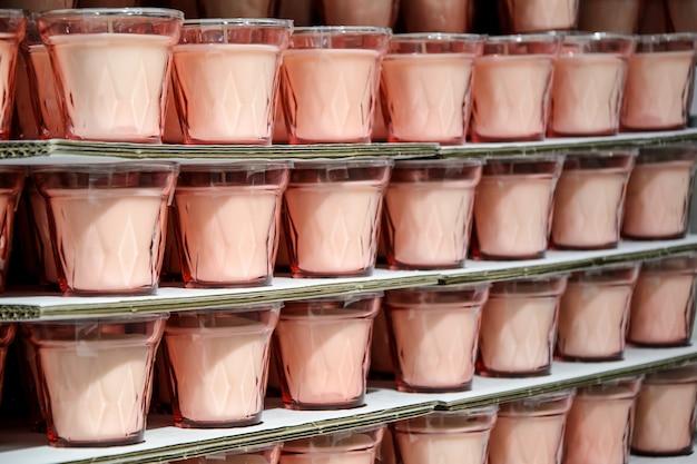 Rack avec beaucoup de bougies roses dans des verres en verre