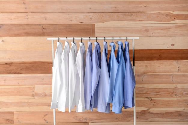 Rack avec des vêtements après le nettoyage à sec sur fond de bois