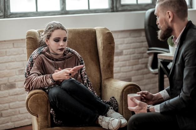 Raconter la rupture. adolescent stressé bouclé avec un maquillage sombre racontant sa rupture avec un psychologue