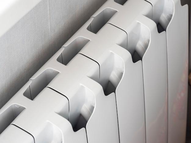 Un radiateur bimétallique est installé sous la fenêtre de la pièce. solutions modernes pour le chauffage central des pièces qui retiennent la chaleur et vous permettent d'économiser de l'argent