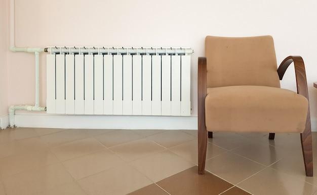 Un radiateur de chauffage blanc en aluminium moderne et un fauteuil marron à la mode sur le fond d'un mur dans un quartier résidentiel.