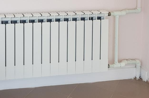Radiateur de chauffage blanc en aluminium moderne sur le fond d'un mur dans un quartier résidentiel.