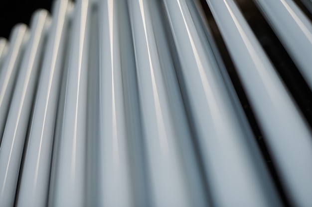 Radiateur de chauffage dans le bureau, gros plan. échangeurs de chaleur blancs. radiateur à vapeur en aluminium et fer. modèle de tuyau.