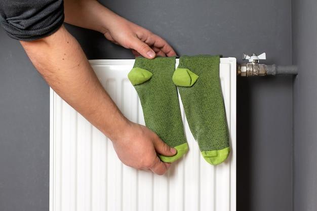 Radiateur de chauffage domestique. la main de l'homme tient des chaussettes qui sèchent sur le radiateur.