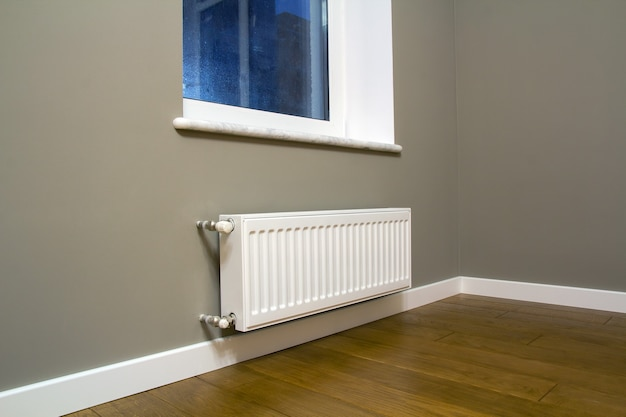 Radiateur de chauffage en métal blanc monté sur un mur gris à l'intérieur d'une pièce