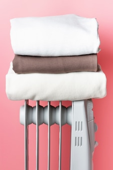 Sur le radiateur, il y a une pile de vêtements contre le mur rose