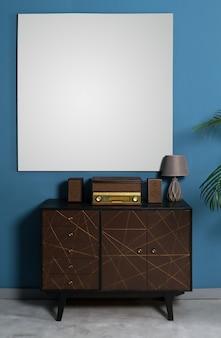 Radio de style rétro sur armoire à tiroirs et cadre blanc vide