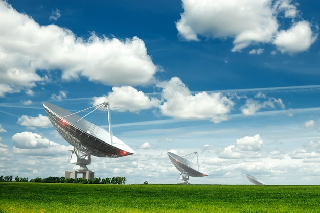 Radio-télescope blanc, une grande antenne parabolique sur un mur de ciel bleu, radar. concept technologique, recherche de vie extraterrestre, écoute de l'espace. milieu mixte, espace copie.