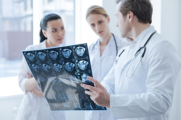 Radiographies concentrées intelligentes qualifiées travaillant au laboratoire et ayant une discussion tout en tenant une photo de tomodensitométrie