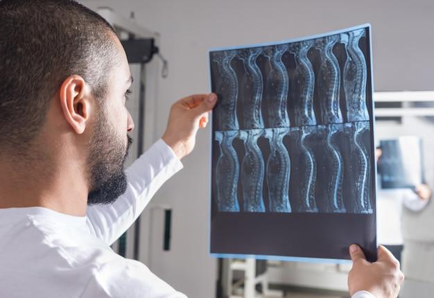 Radiologue analysant l'image aux rayons x avec la colonne vertébrale humaine dans la salle de consultation