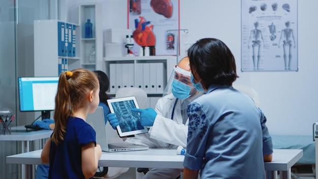 Radiologue expliquant la radiographie à l'aide d'une tablette dans un cabinet médical et une infirmière travaillant sur ordinateur. pédiatre spécialiste avec masque de protection fournissant un examen de traitement radiographique de service de soins de santé