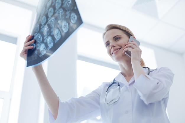 Radiologue positif intelligent féminin travaillant à l'armoire à rayons x tout en examinant la radiographie du cerveau et en utilisant un gadget numérique pour la conversation