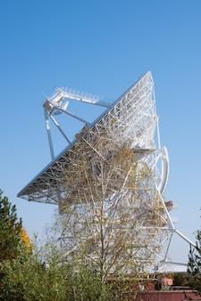 Radiotélescope blanc, grande antenne parabolique sur fond de ciel bleu et d'arbres.