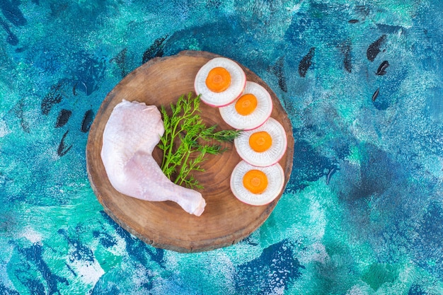 Radis et carottes tranchés à l'aneth et pilon de poulet sur une planche