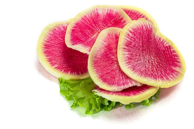 Radis coupé en fines tranches pour salade sur une assiette blanche. isole. copiez l'espace.