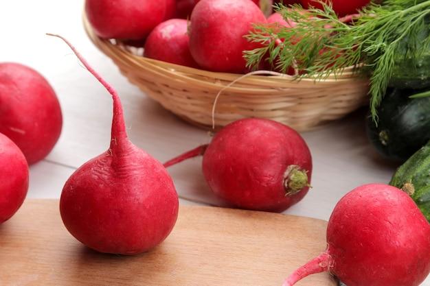 Radis frais. radis de légumes frais de printemps, concombre, oignons verts et légumes verts sur une table en bois blanche. ingrédients pour la cuisson.