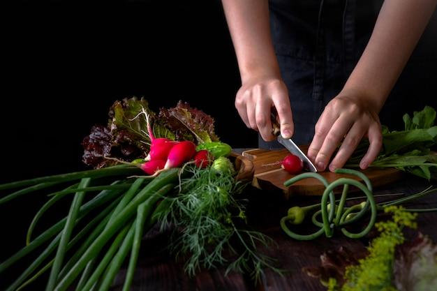 Radis de plumes vert oignon légumes frais et les mains de la jeune fille se prépare sur un fond en bois sombre dans un style rustique avec espace de copie