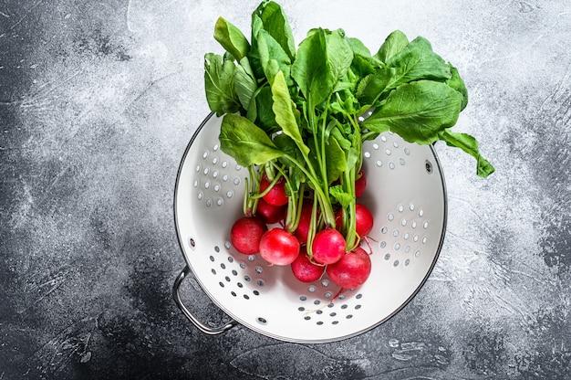 Radis rouges frais dans une passoire blanche. légumes biologiques fermiers. fond gris. vue de dessus