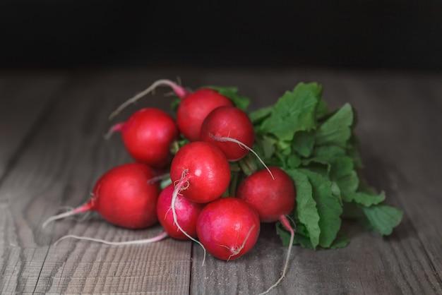 Radis rouges juteux mûrs avec des sommets allongés sur une table en bois.