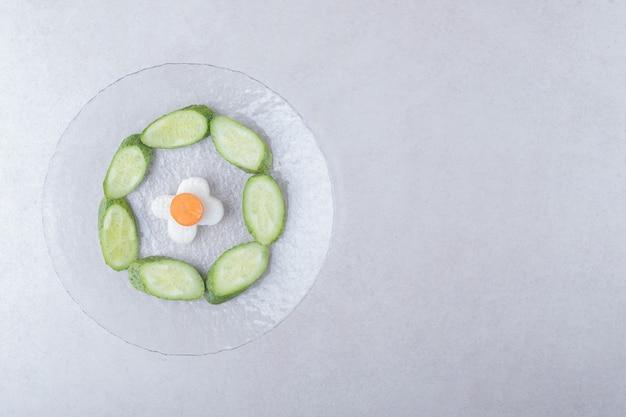 Radis tranché avec carotte à côté de concombre tranché sur plaque de verre sur table en marbre.