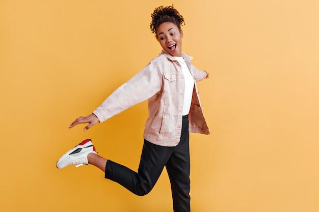 Raffiné jeune femme dansant sur mur jaune