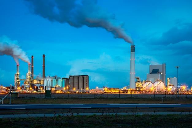 Raffinerie de pétrole dans la nuit à rotterdam, aux pays-bas. pollution par la fumée de l'industrie de raffinage du pétrole.