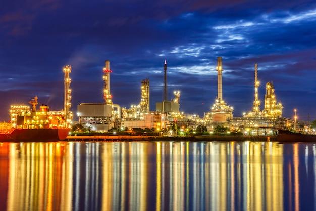 Raffinerie de pétrole le long du fleuve au crépuscule (bangkok, thaïlande)