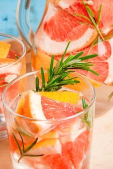 Rafraîchissant cocktail détox d'été de pamplemousse et de romarin, sur une table rustique en bois, copie espace, vue rapprochée