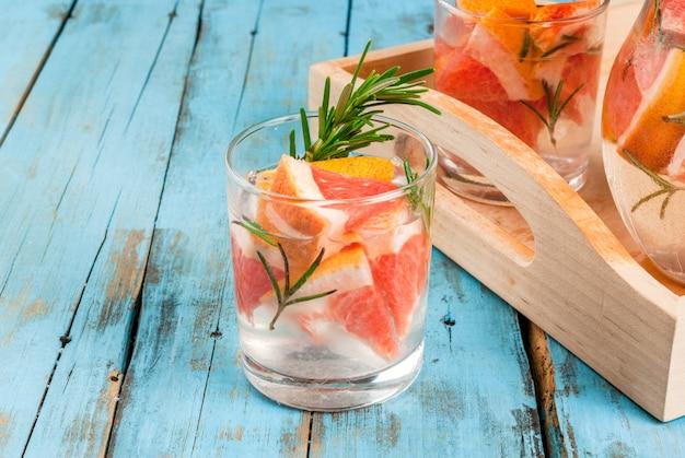 Rafraîchissant cocktail détox d'été de pamplemousse et de romarin, sur une table rustique en bois, espace copie
