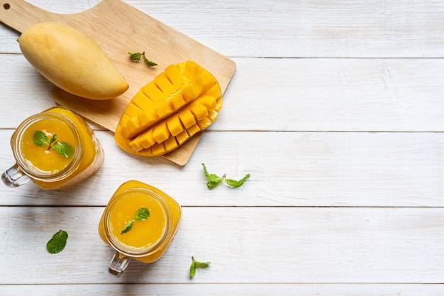 Rafraîchissant smoothies à la mangue en verre avec mangue mûre sur table en bois blanc et copyspace, vue de dessus