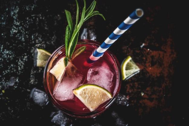 Rafraîchissement alcoolique canneberge rouge et cocktail de citron vert avec romarin et glace, deux verres, vue de dessus de fond sombre