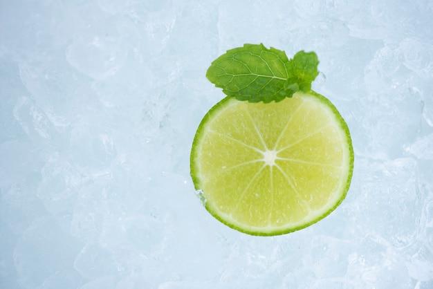 Rafraîchissement d'été de boissons froides fruits frais tranche de citron vert sur glace avec feuille de menthe, vue de dessus