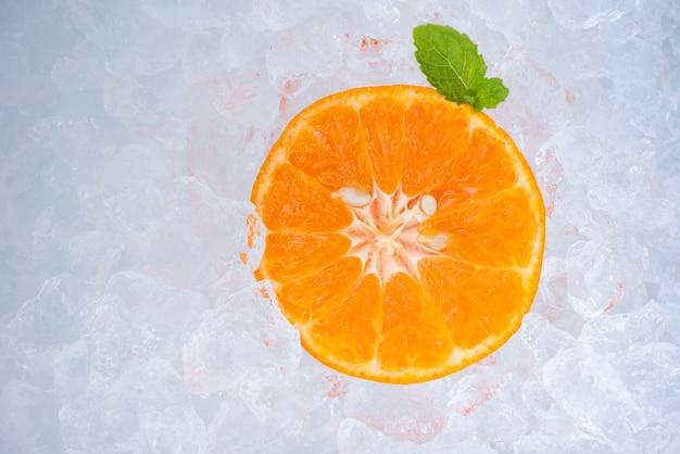 Rafraîchissement d'été de boissons froides tranche d'orange de fruits frais sur glace avec feuille de menthe, vue de dessus